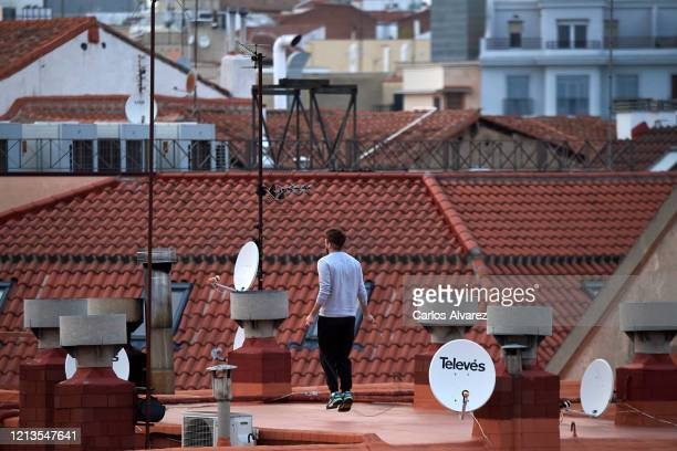 Man does gymnastics on the roof of his house on March 19, 2020 in Madrid, Spain. As part of the measures against the virus expansion the Government...