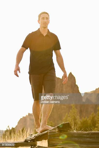 A man does his best to balance while walking on  thin log. (solar flare)