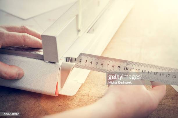 Man does measuring with slide calliper in paper cutter