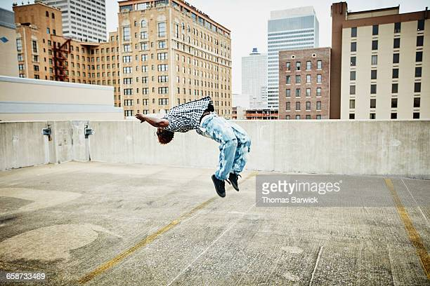 Man doing a backflip on rooftop of building