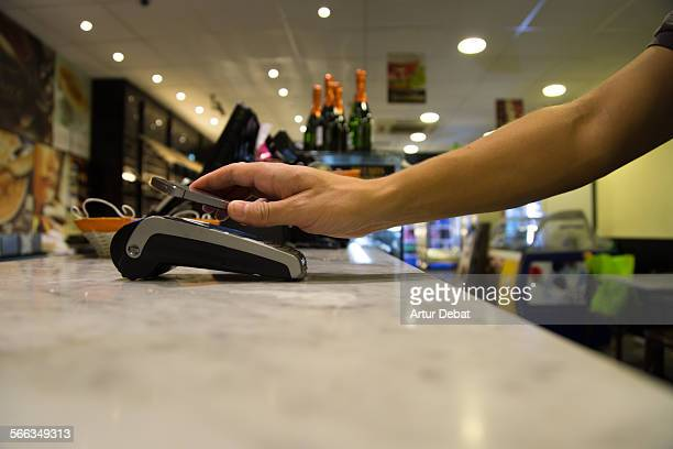 Man doing a contactless payment with smartphone application on a bakery