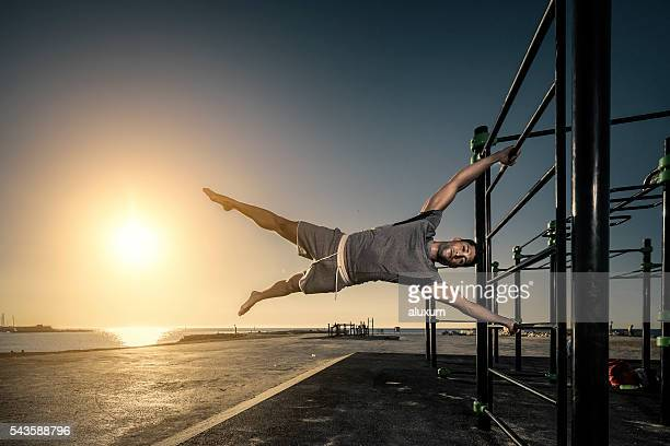 Man doing a flag figure part of his calisthenics routine