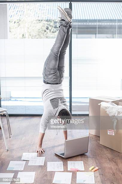 Man doing a handstand at laptop next to cardboard boxes