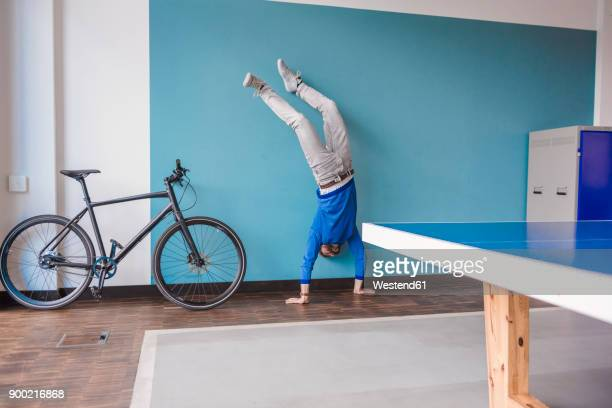 man doing a handstand in break room of modern office - handstand stock pictures, royalty-free photos & images