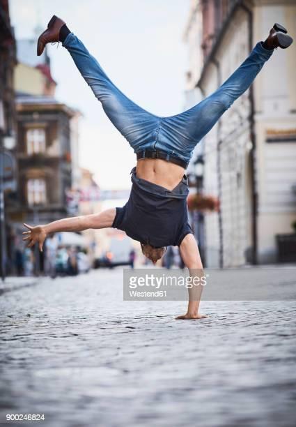 man doing a handstand in the city - artist stock-fotos und bilder