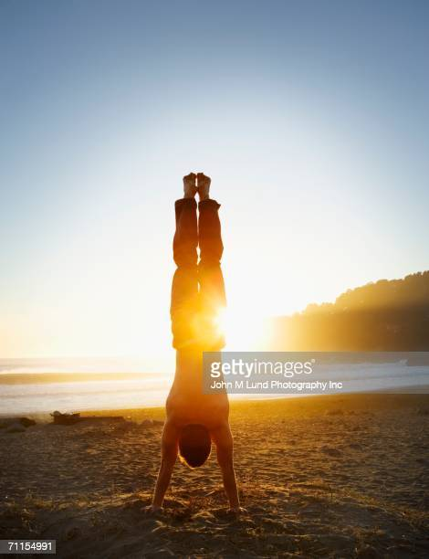 Man doing a handstand on the beach