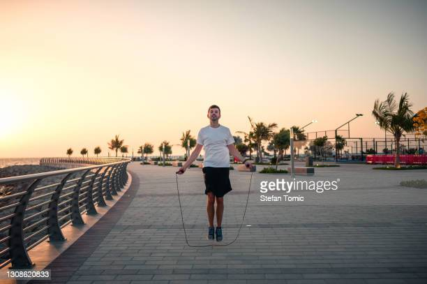 man doing a jumping rope exercise at sunset by the seaside - gulf countries stock pictures, royalty-free photos & images