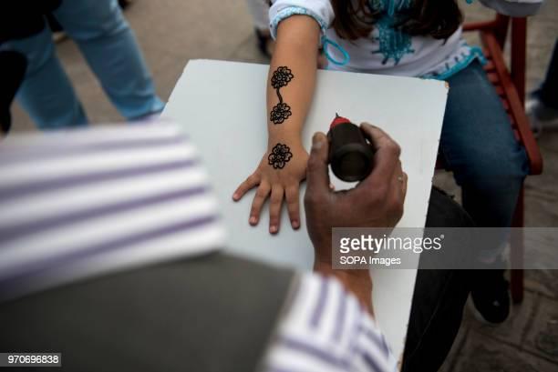 A man doing a temporary black henna tattoo before the public Iftar in Palacio de Congresos Square in Granada During Ramadan Granada Muslim community...
