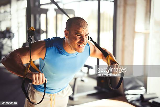 man doing arm exercises with suspension straps at gym. - effort stock pictures, royalty-free photos & images