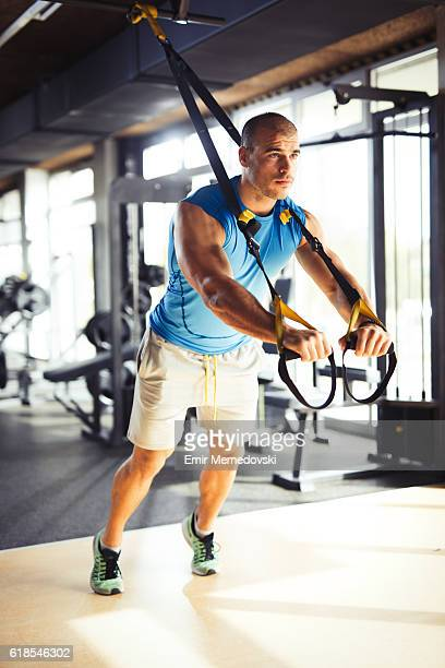 man doing arm exercises with suspension straps at gym. - human arm stock pictures, royalty-free photos & images