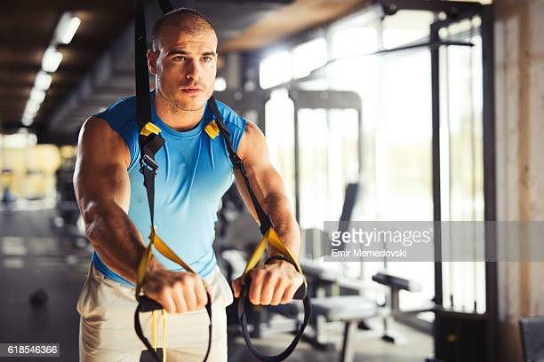 Man doing arm exercises with suspension straps at gym.