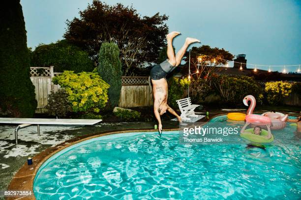 man doing backflip into pool while friends watch during party on summer evening - personas en el fondo fotografías e imágenes de stock
