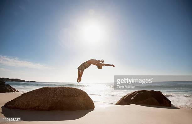 Man doing backflip on beach