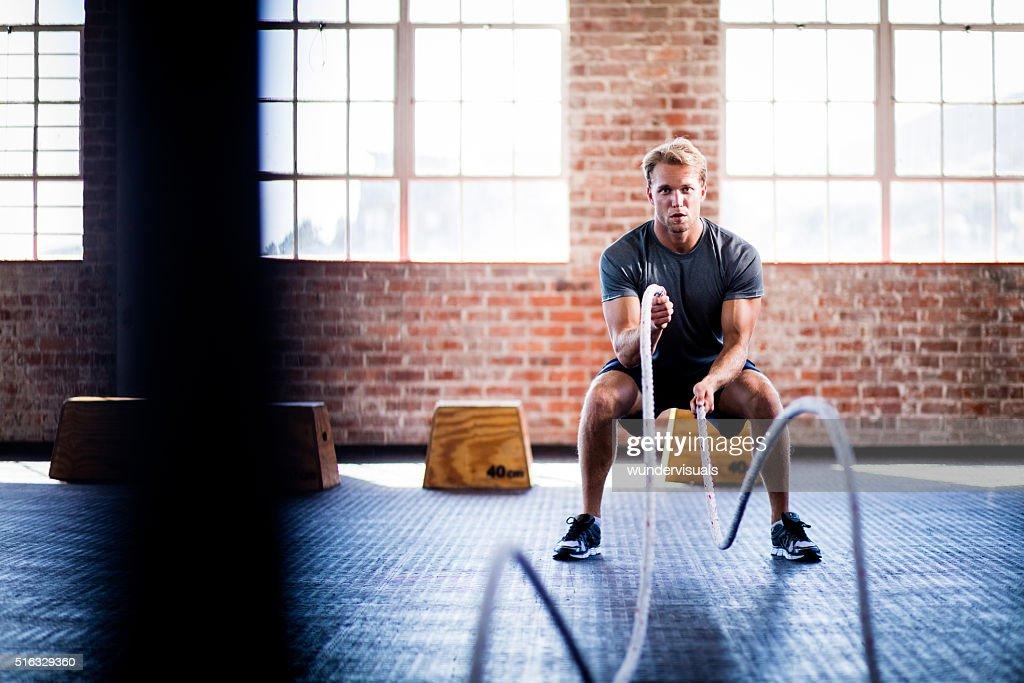Uomo facendo battaglia corde esercizio durante il CrossFit allenamento in palestra : Foto stock