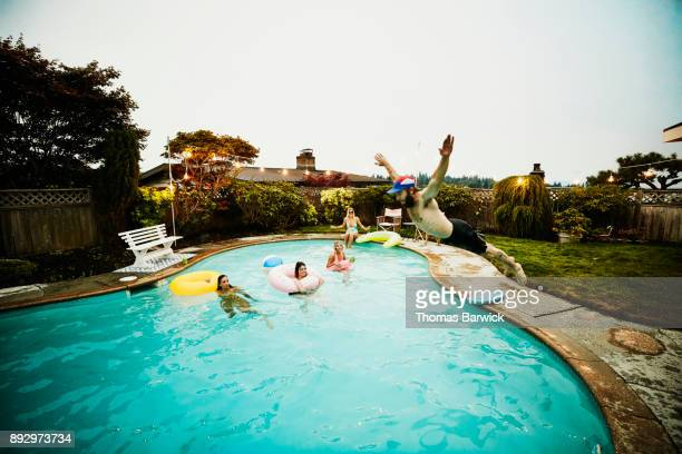 Man doing belly flop into backyard pool during party with friends on summer evening