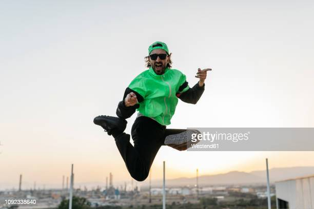man doing breakdance in urban concrete building, jumping mid air - wurf oder sprungdisziplin herren stock-fotos und bilder