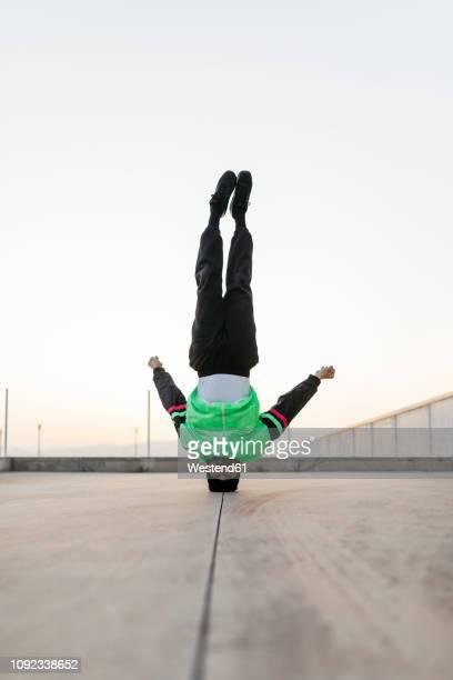 man doing breakdance in urban concrete building, standing on head - artes marciales fotografías e imágenes de stock