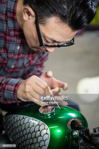 A man doing custom paint on a motorcycle gas tank