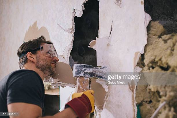 man doing demolition. - demolishing stock pictures, royalty-free photos & images