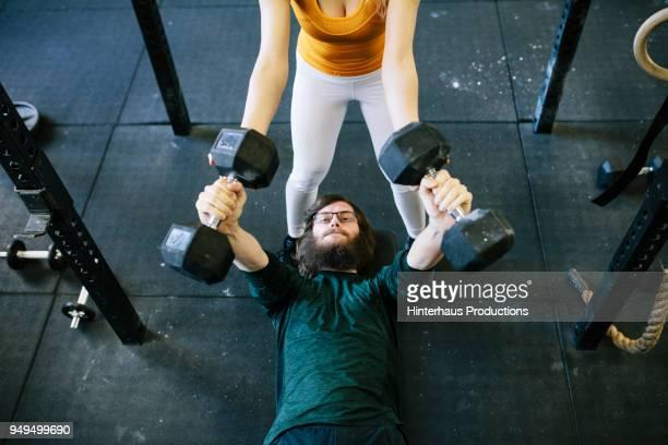 man doing dumbbell exercises at gym - deitado de costas - fotografias e filmes do acervo