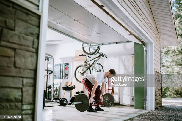 man doing exercise workout in garage - dansstudio stock pictures, royalty-free photos & images