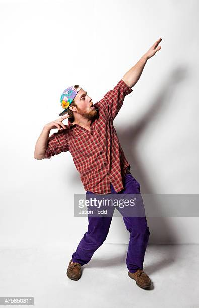 man doing Greek God pose in colorful clothes