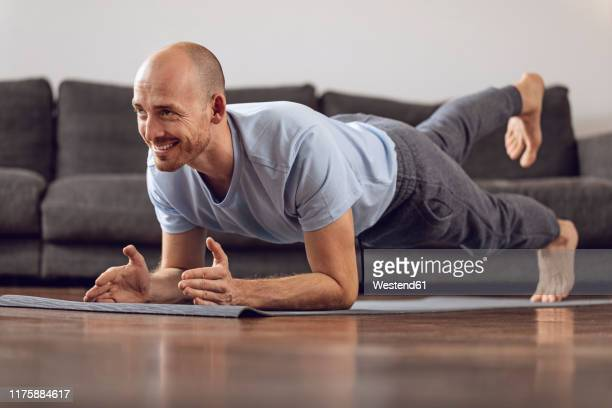 man doing gymnastics at home - colchoneta de ejercicio fotografías e imágenes de stock
