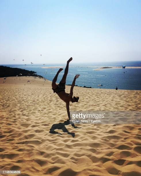 man doing handstand at beach against sky during sunny day - gironde stock pictures, royalty-free photos & images