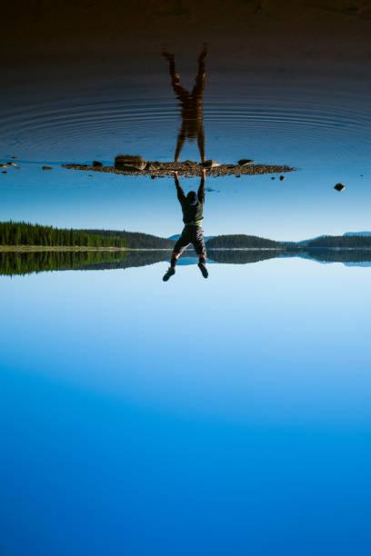 Man doing handstand at McCulloch Lake along the KVR trail,  Okanagan Highlands, British Columbia, Canada