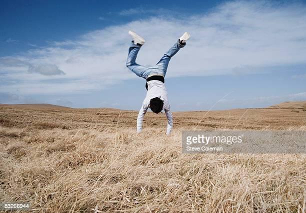 Man doing handstand in field