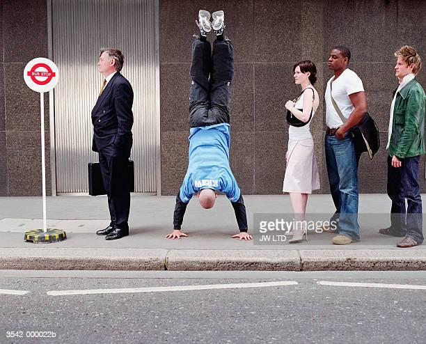 Man doing Handstand in Queue