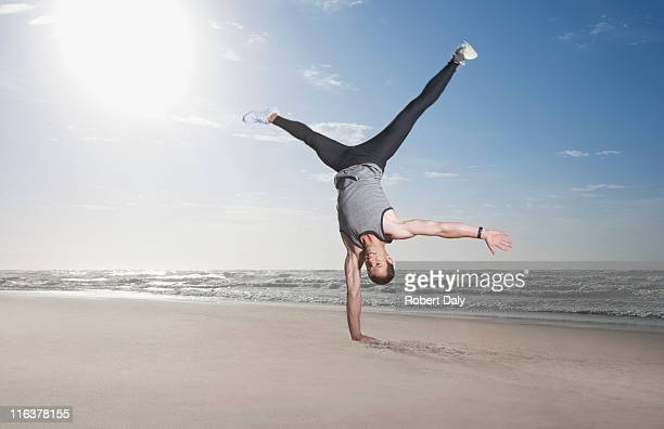 man doing handstand on beach - handstand stock pictures, royalty-free photos & images