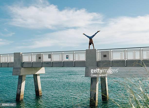 man doing handstand on bridge, south pointe park, south beach, miami, florida, usa - miami beach south pointe park stock pictures, royalty-free photos & images