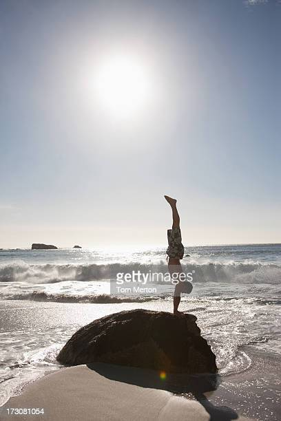 Man doing handstand on rock at beach