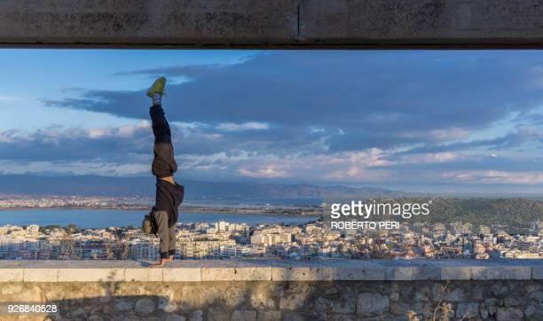 man doing handstand on wall, cagliari, sardinia, italy - le parkour stock-fotos und bilder