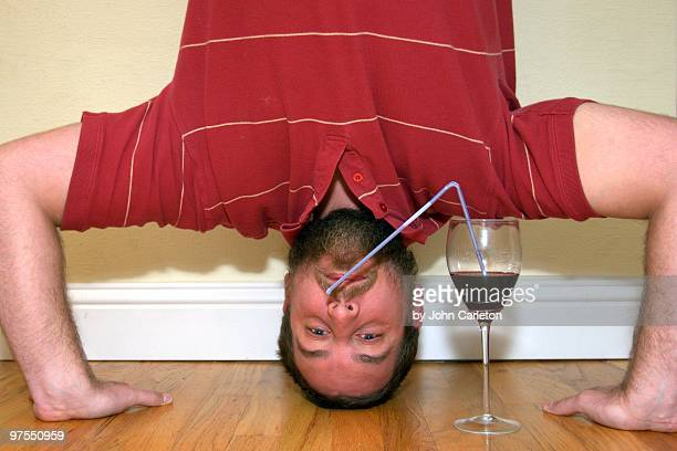 Man doing headstand drinks red wine through straw