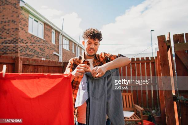 man doing household chores - clothesline stock pictures, royalty-free photos & images