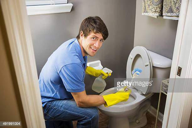 Man doing housework, cleaning bathroom toilet