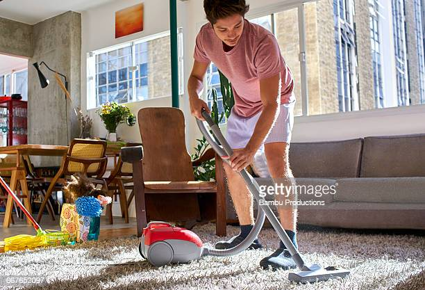 man doing housework vacuuming