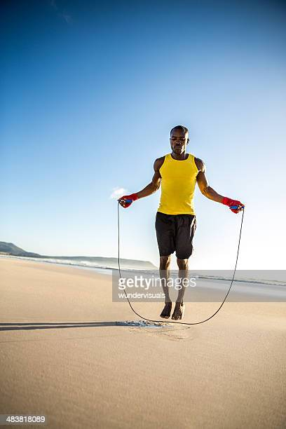 man doing jumping rope at the beach - barefoot black men stock pictures, royalty-free photos & images