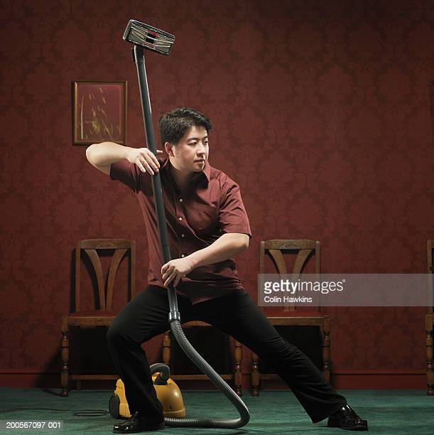 man doing kung fu pose with vacuum cleaner - man cave stock pictures, royalty-free photos & images
