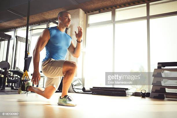 Man doing leg exercises with suspension straps at gym.