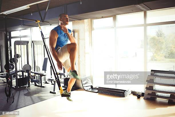man doing leg exercises with suspension straps at gym. - human limb stock pictures, royalty-free photos & images