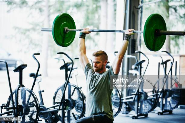 man doing lunges with barbell overhead in gym - barbell stock pictures, royalty-free photos & images