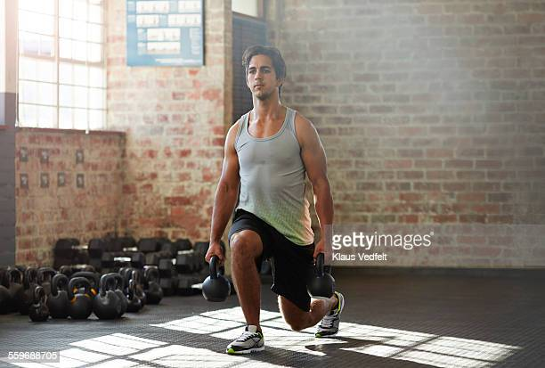 Man doing lunges with kettlebells at urban gym
