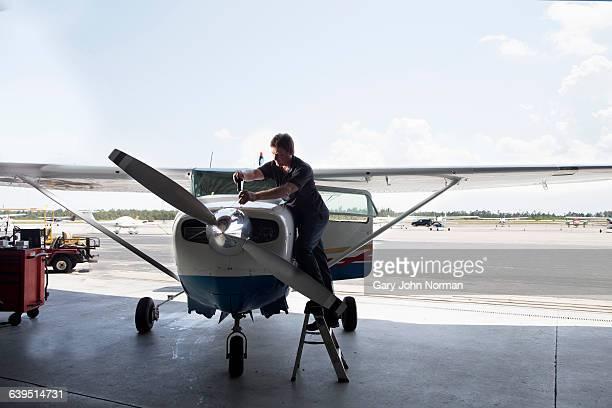 Man doing maintenance work on small airplane