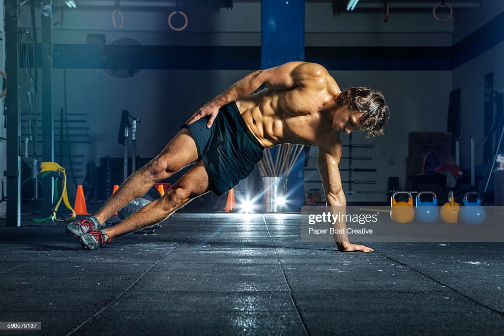Man doing oblique workout with bodyweight : Stock Photo