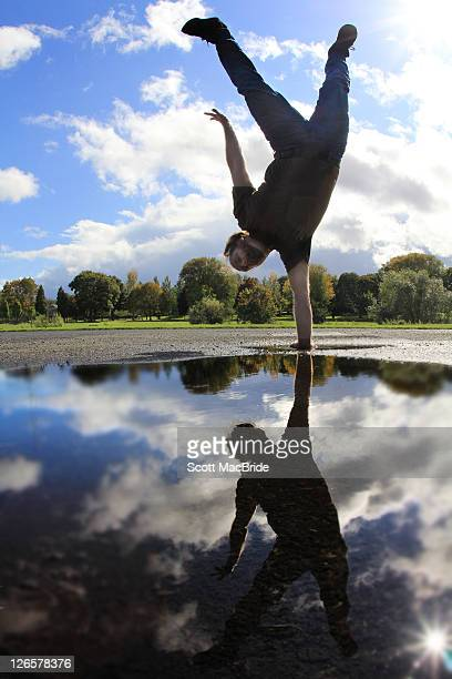 man doing one handed handstand - scott macbride stock pictures, royalty-free photos & images