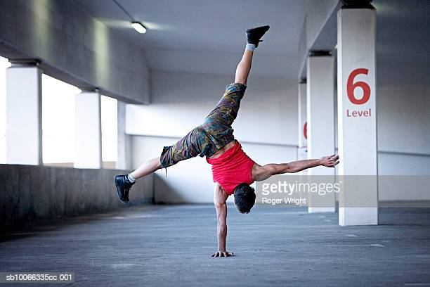Man doing one-handed handstand in multilevel parking garage