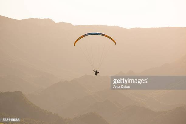 Man doing paragliding on sunset with mountains